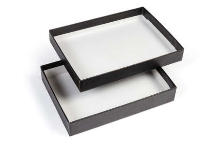 Small black flat rectangular cardboard box with open and inverted lid on a white background