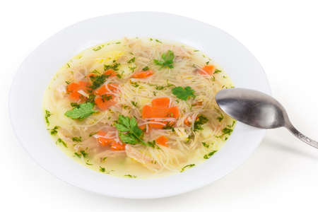 Homemade chicken soup with thin short vermicelli in the white dish and spoon close-up on a white background Фото со стока