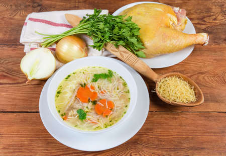 Homemade chicken soup with thin short vermicelli in the white bowl and some raw ingredients on the rustic table Фото со стока