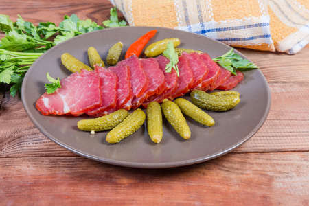 Sliced air-cured and smoked pork neck with pickled gherkins on the brown dish on the rustic table with fresh parsley Фото со стока