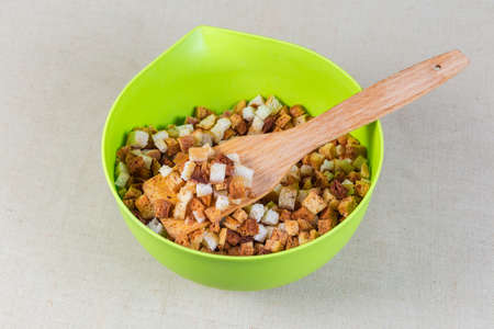 Homemade pieces of dried bread crumbs in the form of small cubes on wooden kitchen spatula in the plastic bowl with the same dried bread crumbs