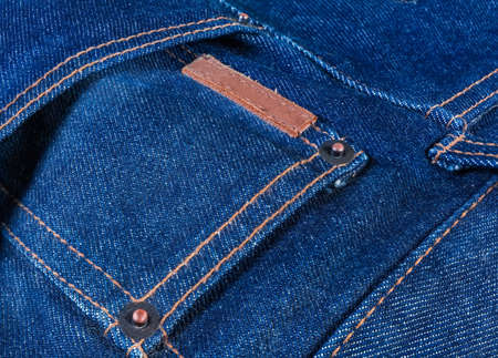 Pocket on the blue jeans with copper rivets and sewed blank small thick leather label close-up