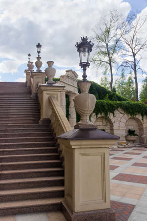 Fragment of stone staircase with carved stone railing and streetlights mounted on on them in park, bottom view