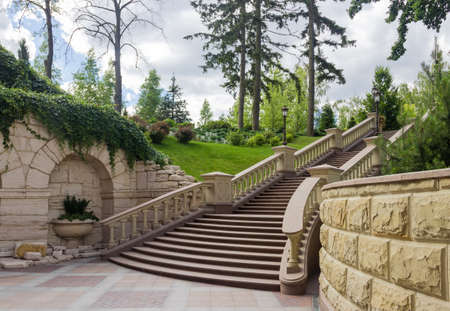Stone staircase with carved stone railing in summer park, bottom view