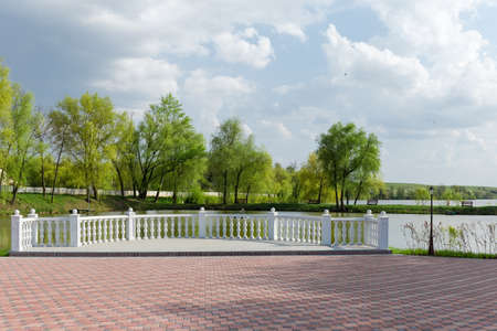 Observation deck with white balustrade over pond and area paved with a tile on a foreground in the park