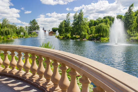 Fragment of stone balustrade with shaped balusters over the decorative pond with fountains in summer park