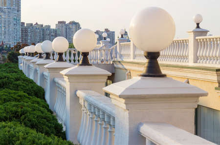 White stone balustrades with shaped balusters and spherical streetlights on open area against the multistory buildings in evening light Banque d'images