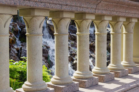 Stone balusters in balustrade on footbridge on a blurred background of small waterfall in park, fragment close-up
