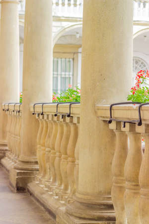 Fragment of the stone balustrade with balusters and columns, decorated with flowers in gallery of an old building, close-up in selective focus
