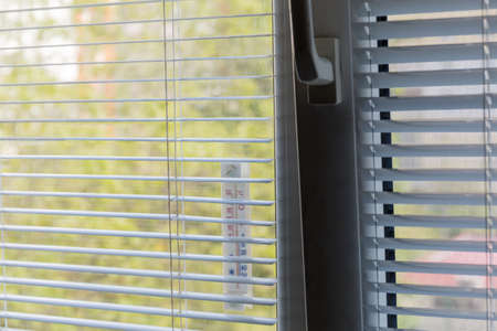 Fragment of the window with horizontal Venetian blinds and attached external thermometer outside, inside view close-up in selective focus