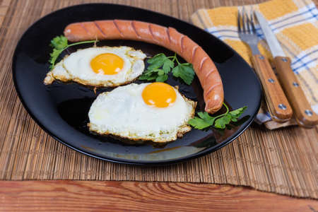 Two fried eggs served sunny side up and grilled long thin sausage on the black dish, close-up in selective focus