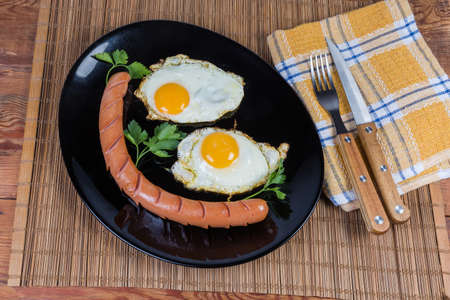 Two fried eggs served sunny side up and grilled long thin sausage on the black dish, fork and knife on napkin on the bamboo table mat, top view
