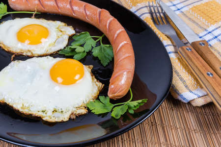 Two fried eggs served sunny side up and grilled long thin sausage on the black dish, fragment close-up in selective focus Foto de archivo