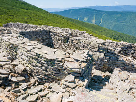 Remnants of the old blindage of the First World War laid out with stones on the mountain slope in the Carpathian Mountains, Ukraine