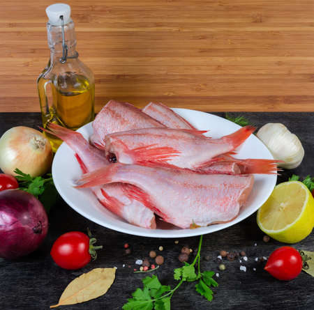 Raw headless gutted carcasses of redfish also known as ocean perch on dish among the spices, fresh vegetables and greens on the black surface  Banco de Imagens
