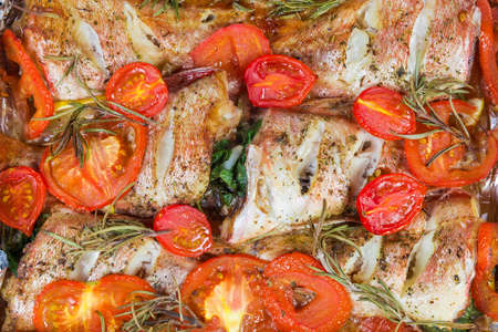 Baked carcasses of the red ocean perch with tomatoes and rosemary, top view of the dish fragment cooked on the oven tray close-up, background
