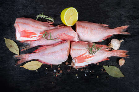 Uncooked headless gutted carcasses of redfish also known as ocean perch among the spices on the black surface, top view Banco de Imagens