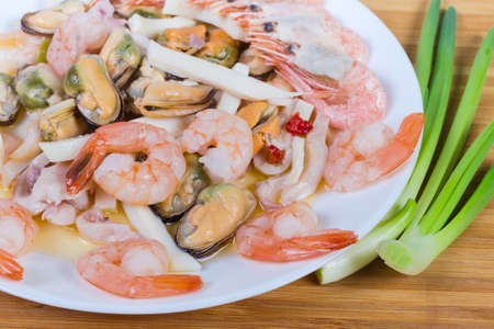 Various cooked seafoods - shrimps, prawn tails, mussels peeled from shells, calamari slices on the white dish, green onion on the wooden surface, fragment close-up Banco de Imagens - 148160478