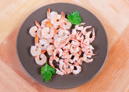 Cooked peeled tails of king prawns and usual shrimps on the brown dish on the wooden surface, top view
