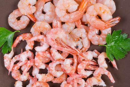 Cooked peeled tails of king prawns and usual shrimps on the brown dish, fragment top view, background Banco de Imagens