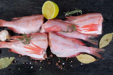 Raw headless gutted carcasses of redfish also known as ocean perch among the spices on the black surface, top view close-up