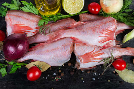 Raw redfish carcasses among the spices, vegetables and greens close-up Banco de Imagens