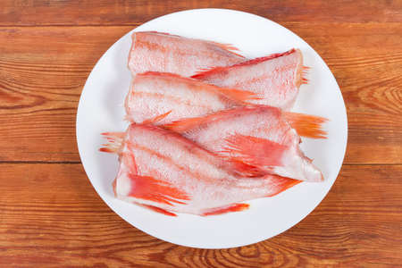 Raw headless gutted carcasses of redfish also known as ocean perch on the dish on the rustic table, top view Banco de Imagens
