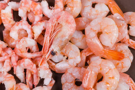 Cooked peeled shrimps tails of two varieties - king prawns and usual shrimps on the brown dish, fragment close-up, background