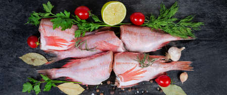 Raw headless gutted carcasses of redfish also known as ocean perch among the spices, fresh vegetables and greens on the black surface, panoramic view from above
