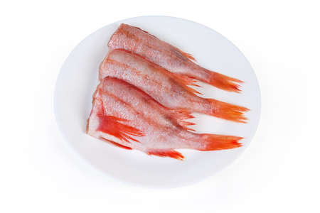 Uncooked headless gutted carcasses of redfish also known as ocean perch or Norway haddock on the white dish on a white background
