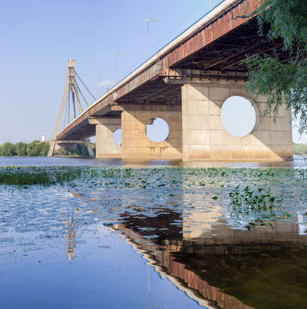 Modern road cable-stayed bridge over river with concrete pylon and steel cables, bottom view from the water. Pivnichnyi  Bridge across Dnieper River, Kyiv, Ukraine