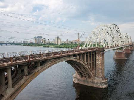 Railroad arch bridge built of stone, concrete and steel over the river, fragment. Darnytskyi Railroad Bridge across Dnieper River, Kyiv, Ukraine