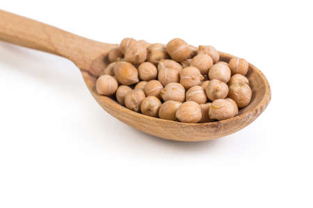 Whole uncooked yellow chickpeas in the wooden spoon on a white background, fragment close-up in selective focus 写真素材
