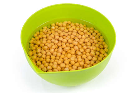 Uncooked yellow chickpeas soaked in cold water in the green plastic kitchen bowl for subsequent faster its preparation, on a white background