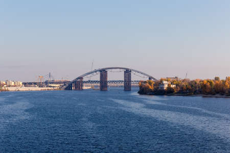 Metro-automobile tied arch bridge with arch-shaped superstructure over river during construction against the other bridges in autumn. Podilsko-Voskresensky Bridge across Dnieper River, Kyiv, Ukraine