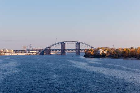 Pont en arc lié Metro-automobile avec superstructure en forme d'arche au-dessus de la rivière pendant la construction contre les autres ponts en automne. Pont Podilsko-Voskresensky sur le fleuve Dniepr, Kiev, Ukraine