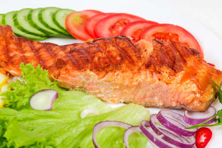 Grilled piece of the trout fillet among the vegetables and greens on the dish, fragment close-up in selective focus Reklamní fotografie