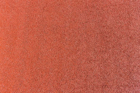 Background of red shock absorbing coatings made from rubber chips on the outdoor sports field, top view under sunlight, texture