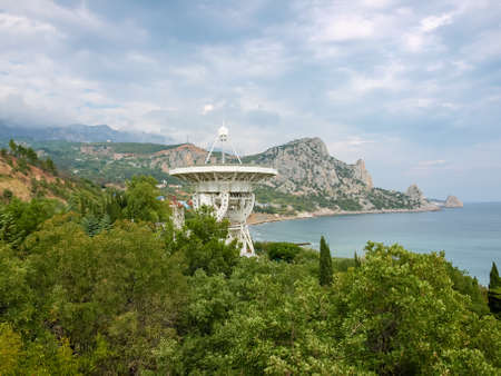 Large parabolic antenna of the radiotelescope among the trees on a sea coast on a background of mountains and cloudy sky, Simeiz Observatory
