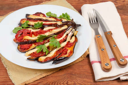 Baked eggplant partly sliced along and stuffed with tomatoes and cheese on white dish, cutlery on napkin on the old rustic table, close-up