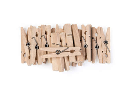 Pile of new wooden clothespins spring type on a white background, top view