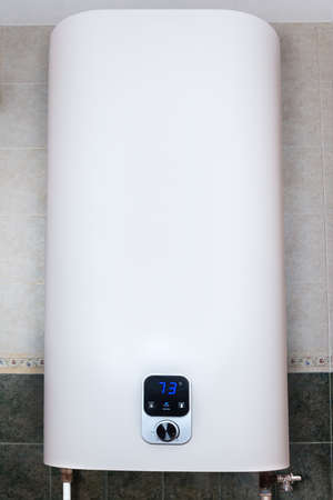Household electric tank-type water heater, so called storage water heater hanging on the tiled wall vertically