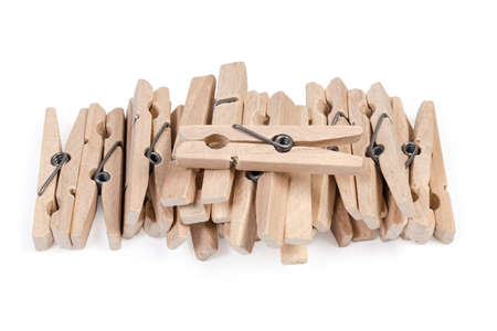 Pile of new wooden clothespins spring type on a white background