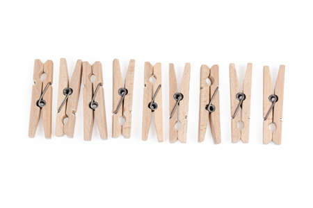 New wooden clothespins spring type laid out in a row on a white background, top view