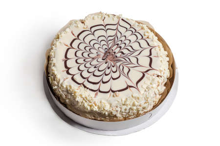 Whole round cake with white and milk chocolate decoration on the paper stand on a white background lit on the right