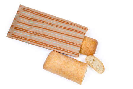 One partly cut ciabatta and whole ciabatta half bagged in paper packing bag on a white background, top view