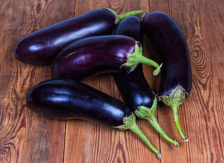 Small pile of raw ripe harvested purple conventional eggplants on the old rustic table