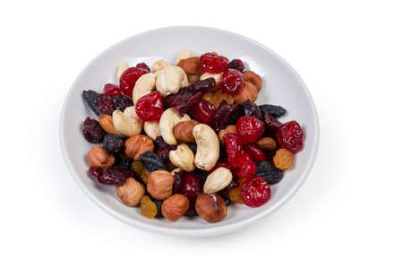 Mix of different nuts, dried fruits and berries on the white saucer on a white background 版權商用圖片