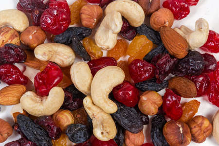 Mix of different nuts, dried fruits and berries close-up on a white surface, top view, background 版權商用圖片