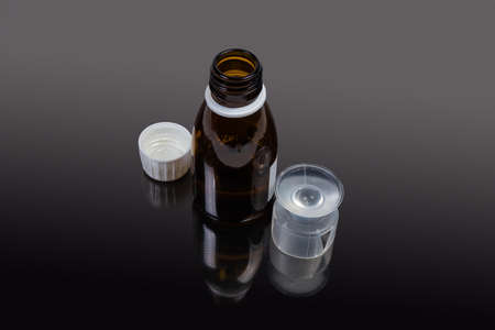 Small brown glass bottle with open lid of liquid medicine, plastic measuring cup on the dark reflective surface